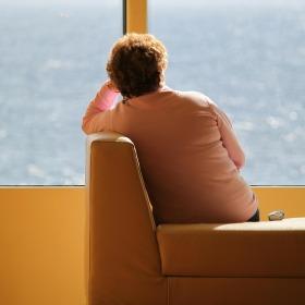 Mujer sola en el interior de una vivienda, mirando por la ventana.